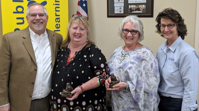 Gary Branson (left) of Marion Public Library, presented recognition of Volunteer of the Year to Vicky Branson and Valerie Mettler, two of the four originators of the BookMarks group of the Marion Public Library. Missing from the photo are Denise Iams and Chad Schnitzler who were the other two volunteers involved. Diane Watson (right) is the library liaison to the BookMarks group.