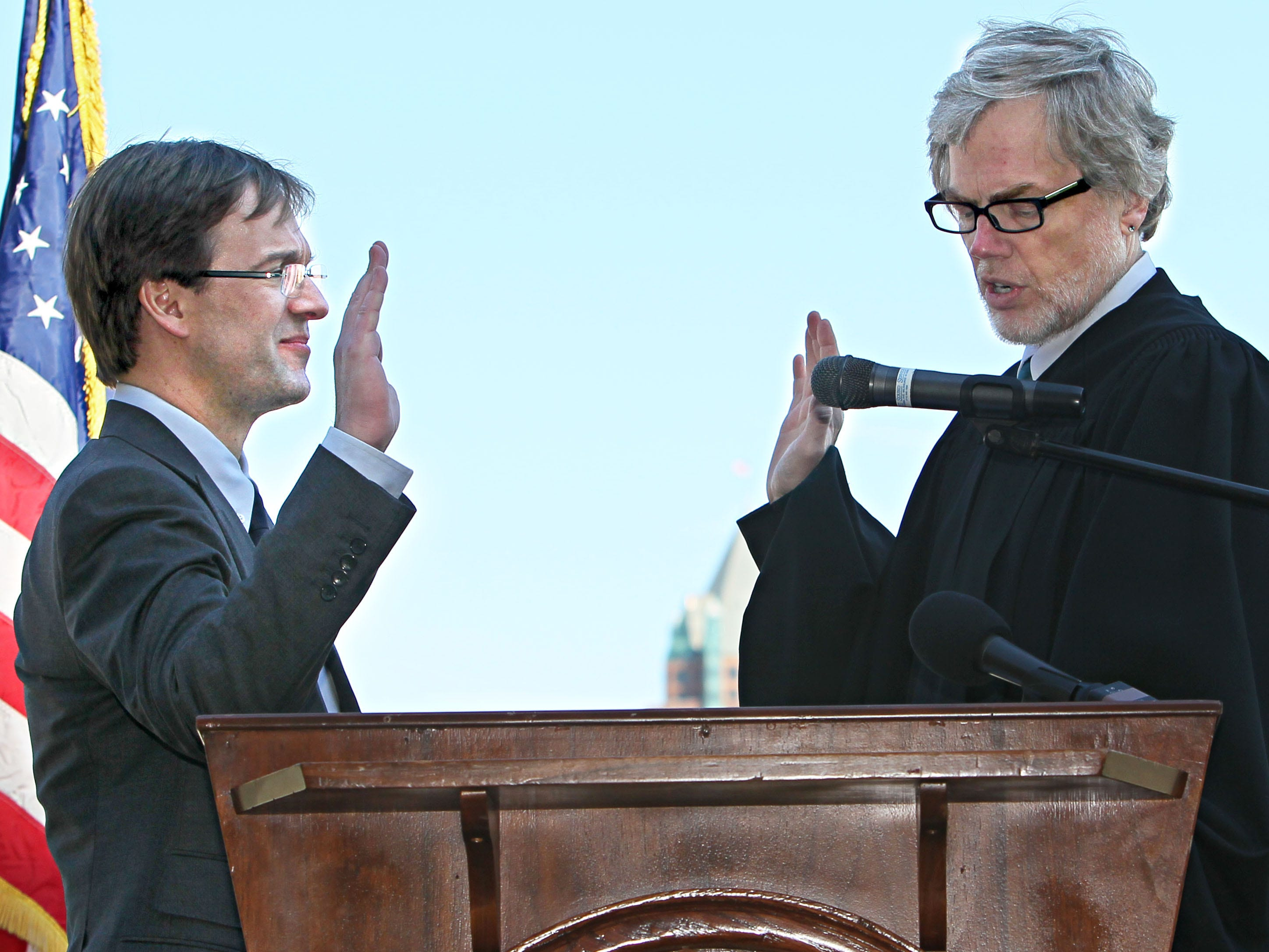 2012: Milwaukee County Executive Chris Abele is sworn in by Milwaukee County Chief Judge Jeffrey A. Kremers (right).  The ceremony was held in MacArthur Square.
