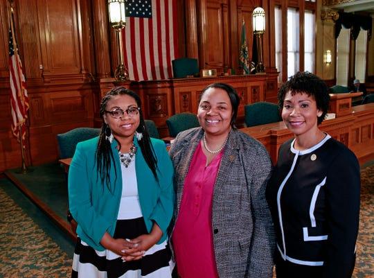 Milwaukee Alderwomen, from left,  Chantia Lewis, Milele Coggs and Nikiya Dodd pose inside the Common Council chambers at Milwaukee City Hall.