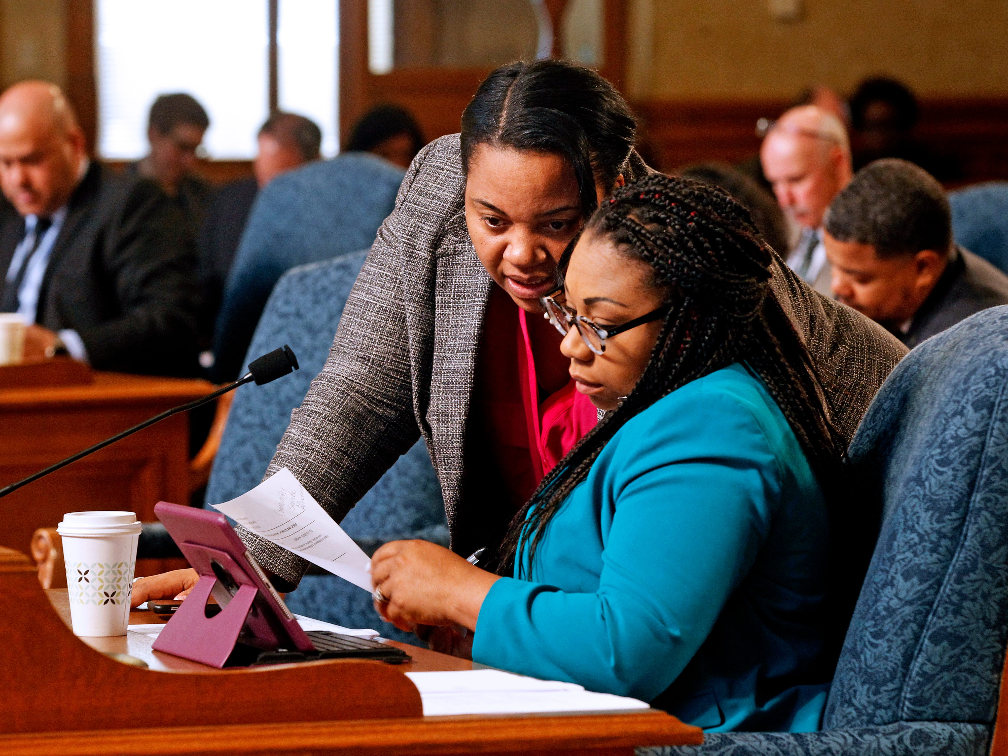 Milwaukee Alderwomen Milele Coggs, left, and Chantia Lewis talk during a Common Council meeting at Milwaukee City Hall.
