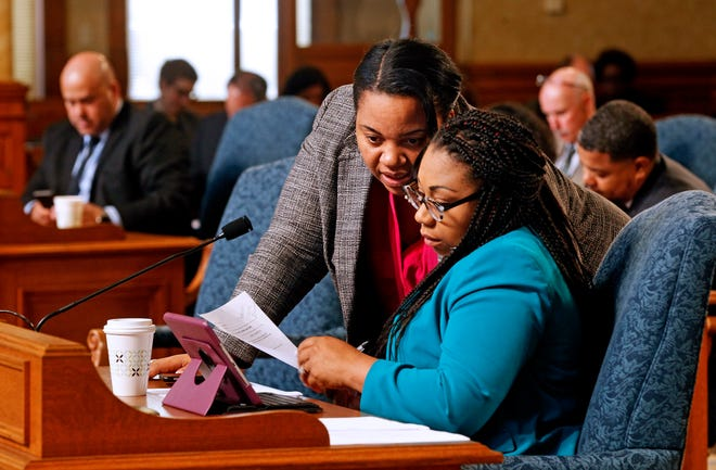Milwaukee Alderwomen Milele Coggs (left) and Chantia Lewis talk in early May inside the Common Council chambers at Milwaukee City Hall.
