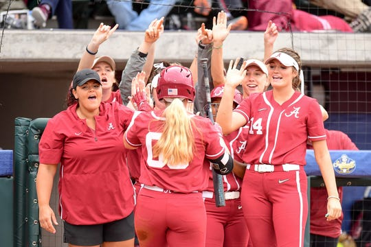 Alabama softball player Maddie Morgan (No. 00) is greeted by Montana Fouts (No. 14) and other teammates and coaches.