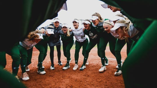 Members of the Colorado State softball team huddle on the field.