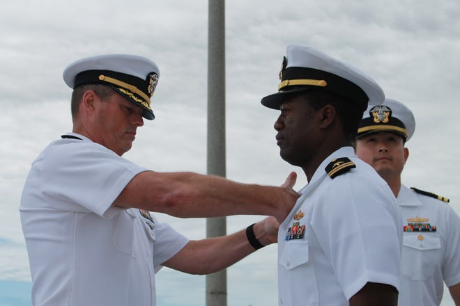 Cmdr. William Swinford pins Lt. Antionne Winston with a command pin as he assumes command of Coastal Riverine Squadron Three Bravo Company Crew One during an assumption of command ceremony onboard Naval Amphibious Base Coronado.