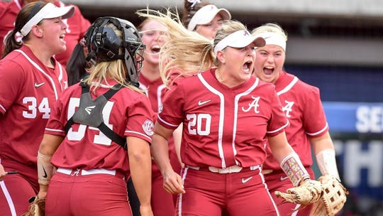 Alabama softball player Sarah Cornell (No. 20) screams while surrounded by teammates.