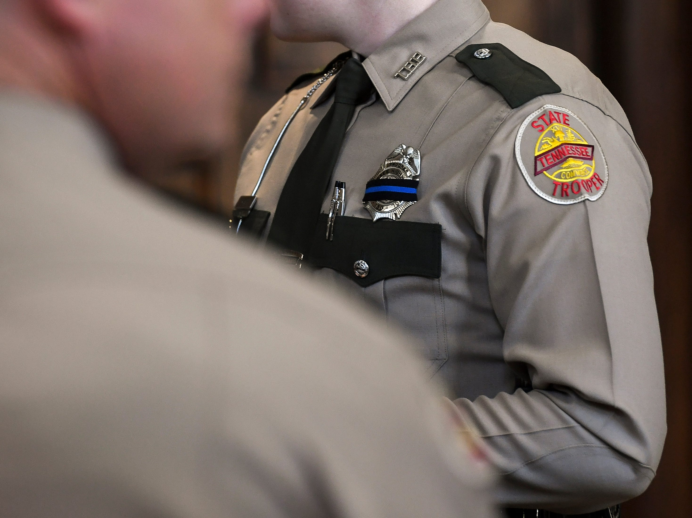 A Tennessee State Trooper wears a mourning band on her badge before the funeral service for Tennessee State Trooper Matthew Gatti at West Jackson Baptist Church in Jackson, Tenn., Monday, May 13, 2019. Gatti died in the line of duty in an accident while responding to a car fire on I-40 in Madison County on May 6.