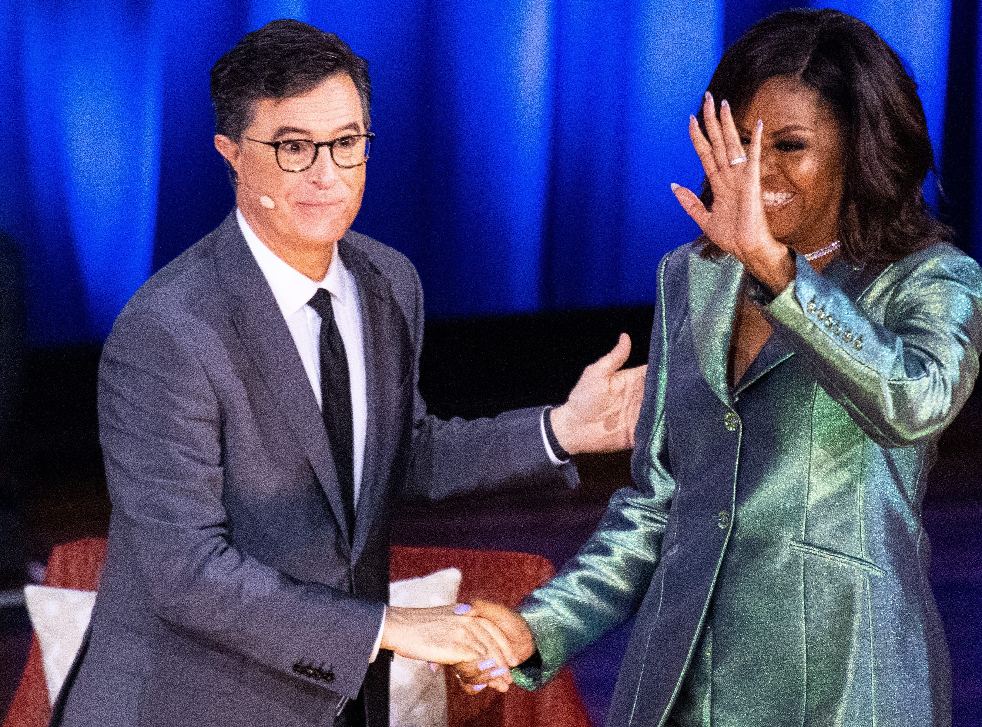 Michelle Obama is greeted by Stephen Colbert during her Becoming: An Intimate Conversation with Michelle Obama event at Ryman Auditorium Sunday, May 12, 2019, in Nashville, Tenn.
