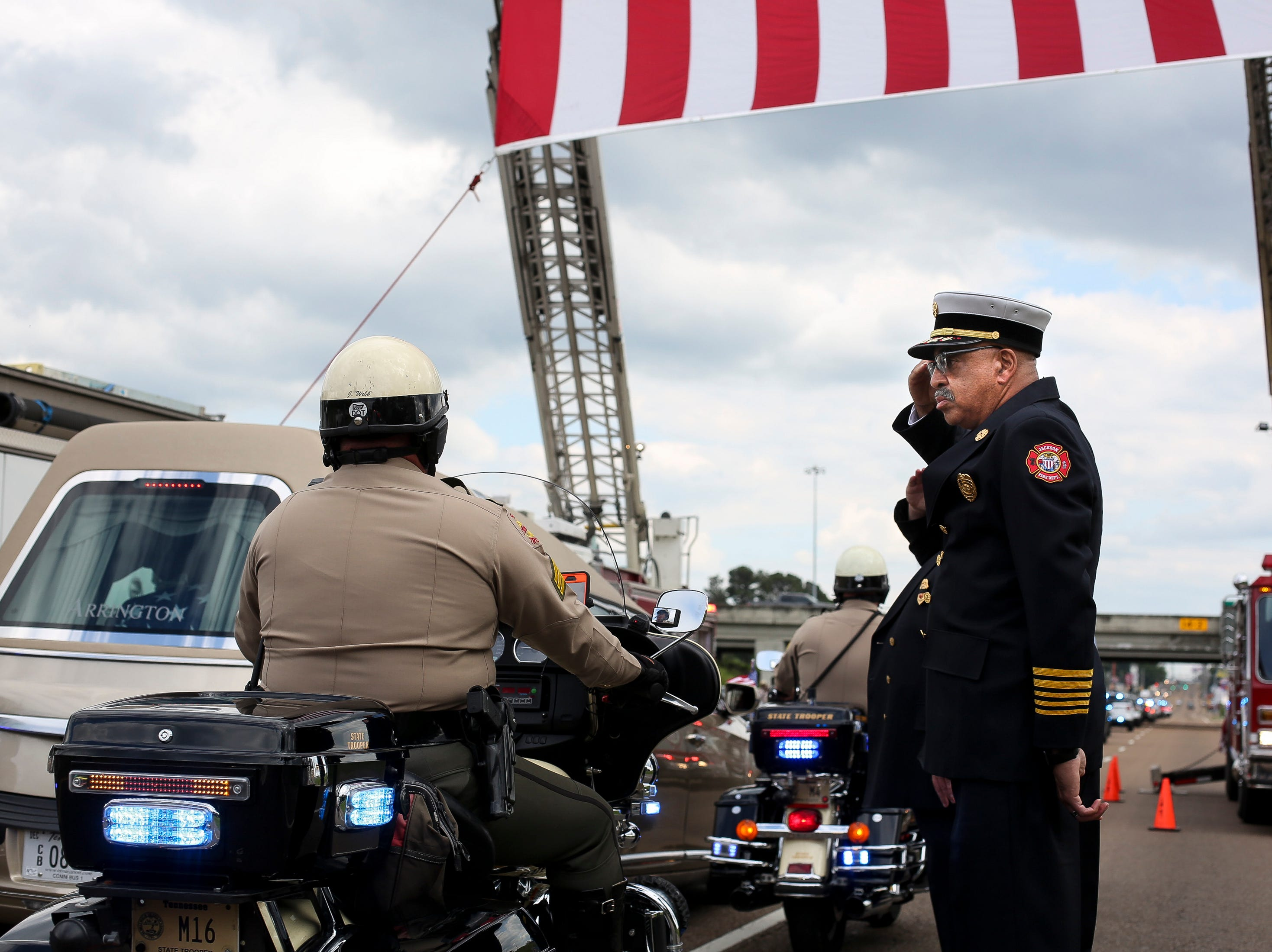 Jackson Fire Department Chief Darryl Samuels salutes the hearse as the funeral procession for Tennessee State Trooper Matthew Gatti passes down U.S. Route 45 in Jackson, Tenn., Monday, May 13, 2019. Gatti died in the line of duty in an accident while responding to a car fire on I-40 in Madison County on May 6.