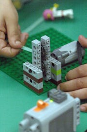 A student plays with Legos in a STEM class.