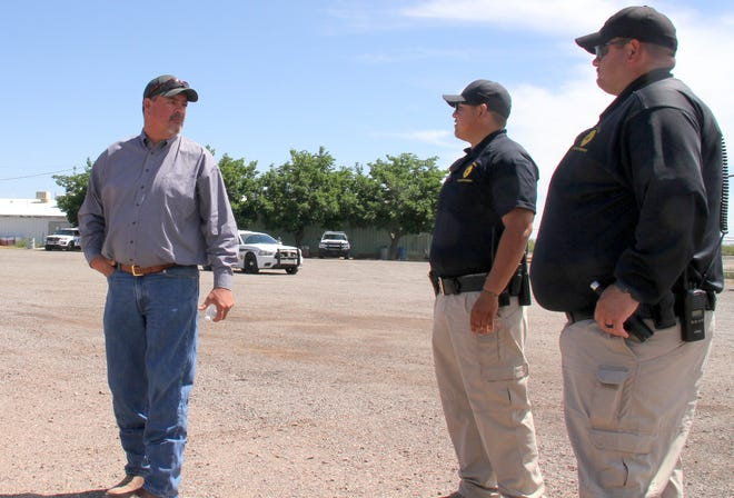 City of Deming Administrator Aaron Sera, left, visits with city code enforcers who are entrusted to securing the gate at the Southwestern New Mexico State Fairgrounds.
