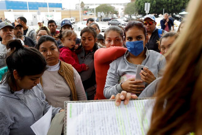 In this Oct. 23, 2018, file photo, women in Tijuana, Mexico, look on as numbers and names are called to from a list of asylum seekers who want to cross the border into the United States. Tijuana is the busiest border crossing, with about 70,000 people crossing each way every day in cars and about 40,000 on foot.