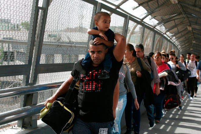 In this April 29, 2019, photo, Cuban migrants are escorted by Mexican immigration officials in Ciudad Juárez, Mexico, as they cross the Paso del Norte International bridge to be processed as asylum seekers on the U.S. side of the border. Burgeoning numbers of Cubans are trying to get into the U.S. by way of the Mexican border, creating a big backlog of people waiting on the Mexican side for months for their chance to apply for asylum.