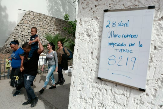 """In this April 29, 2019 photo, Cuban migrants line up to be called by Mexican immigration officials in Ciudad Juárez, Mexico, to be taken across the Paso del Norte International bridge to be processed as asylum seekers on the U.S. side of the border. The sign on the wall reads in Spanish """"April 28 The last number to called in the afternoon is 8219""""."""