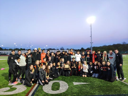 The Northville boys and girls track teams pose with the KLAA West Division trophies and girls KLAA conference trophy.