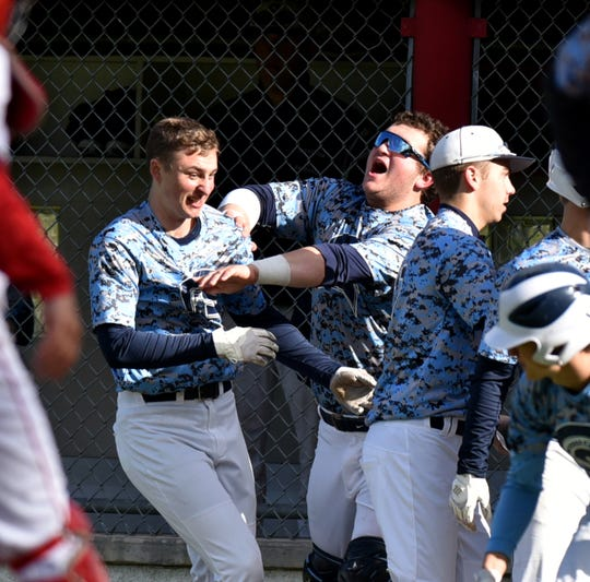 Nate Waligora, left, gets a friendly teammate shove from catcher Bobby Calvin after scoring a run in the Spartans' May 13 game at John Glenn.