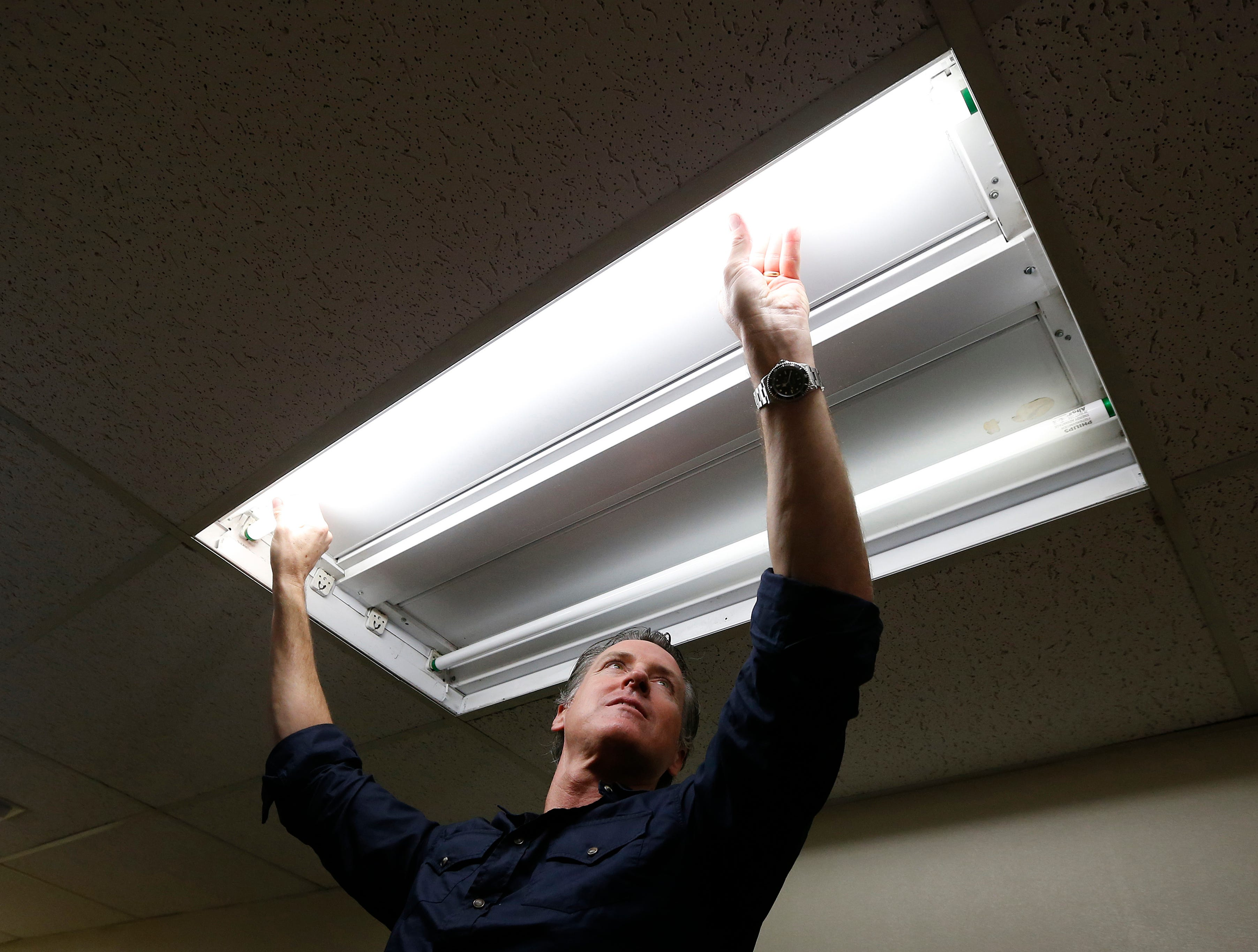 Gov. Gavin Newsom replaces a light bulb while helping the maintenance staff at American River College on Wednesday, May 1, 2019, in Sacramento.