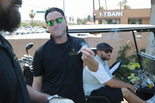Perry Holcomb passes a joint between his group of golfers at the Coachella Valley Cannabis Alliance Network's charity golf tournament, Palm Desert, Calif., May 11, 2019.