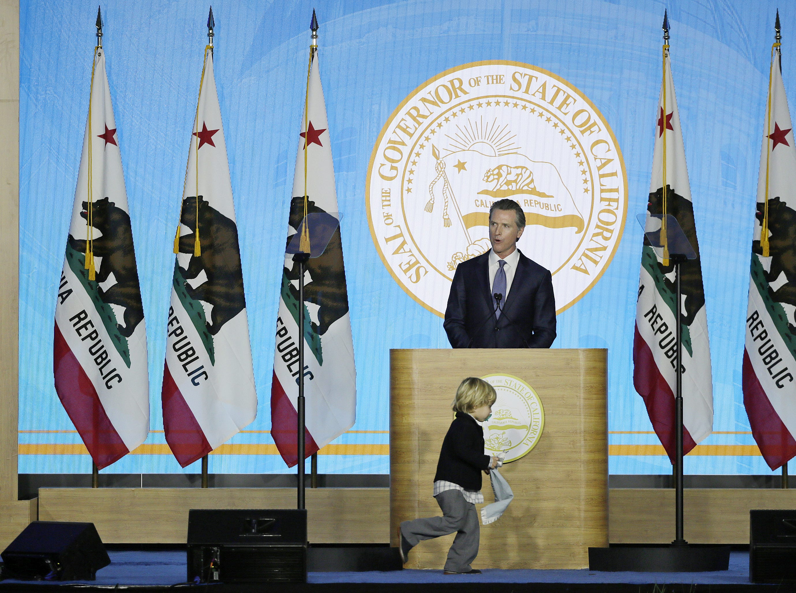 Gov. Gavin Newsom speaks during his inauguration as his son Dutch runs around the podium on Monday, Jan. 7, 2019, in Sacramento.