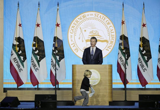 Gov. Gavin Newsom speaks during his inauguration as his son Dutch runs around the podium on Monday, Jan. 7, 2019, in Sacramento.