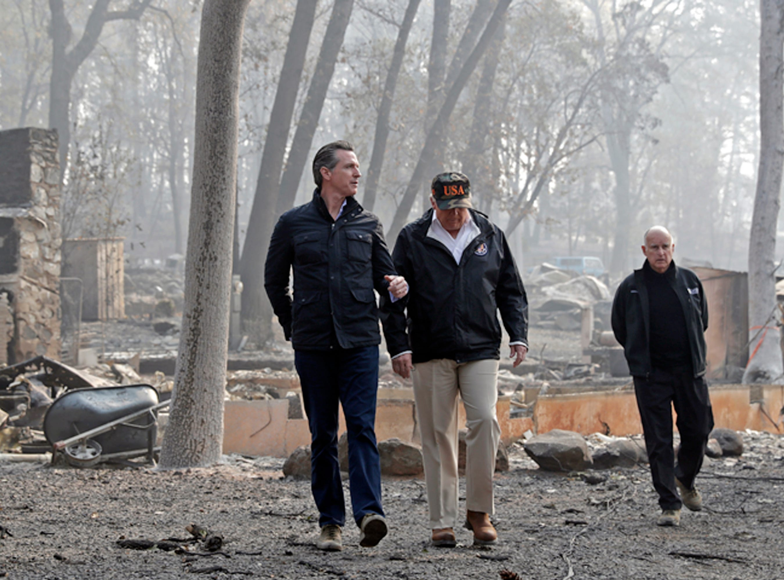 President Donald Trump talks with California Gov.-elect Gavin Newsom, left, on Nov. 17, 2018, as California Gov. Jerry Brown, walks at right during a visit to a neighborhood destroyed by the Camp wildfire in Paradise.