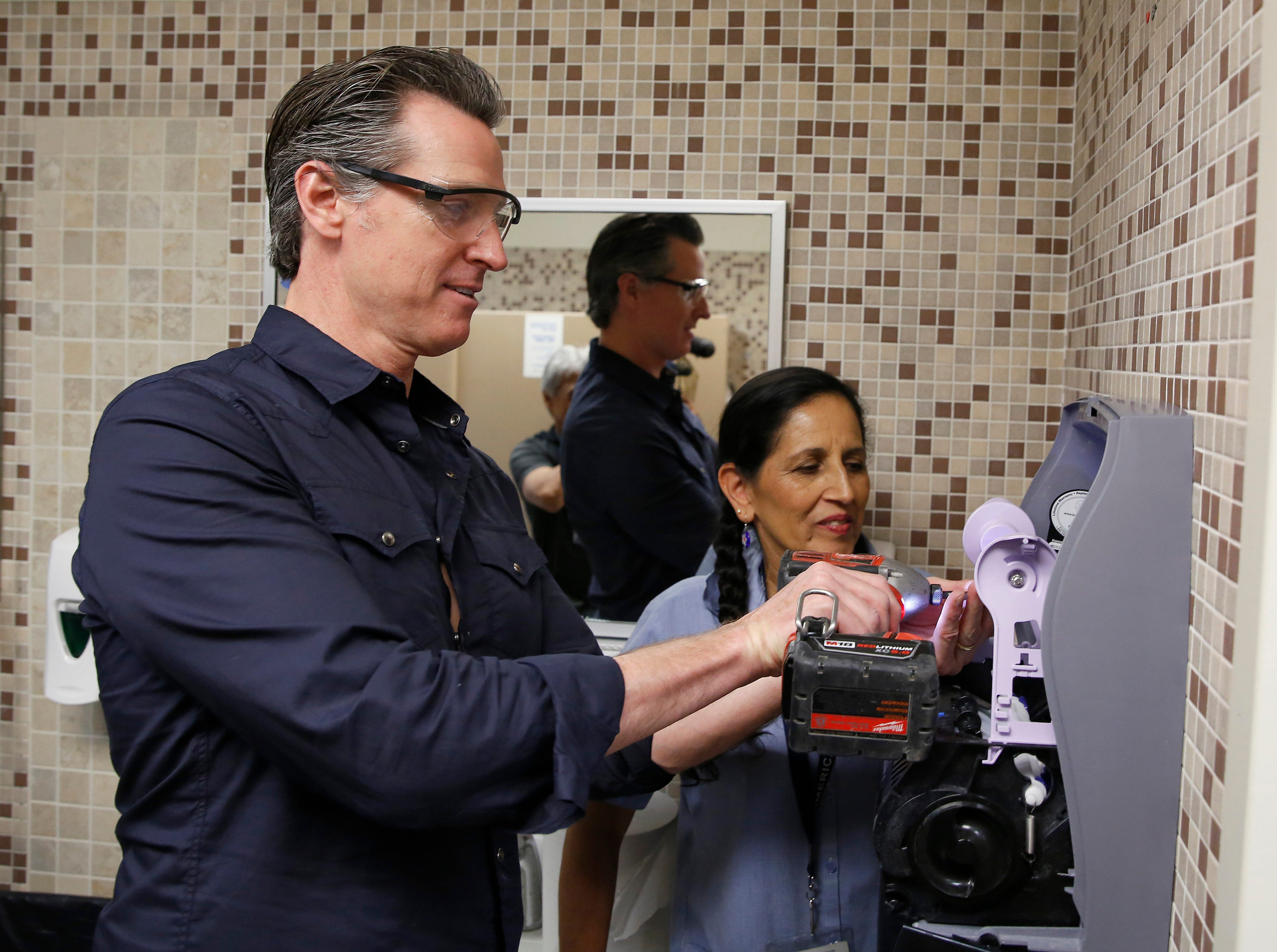 Gov. Gavin Newsom helps custodian Maria Arambula replace towel dispenser in a restroom at American River College on Wednesday, May 1, 2019, in Sacramento.