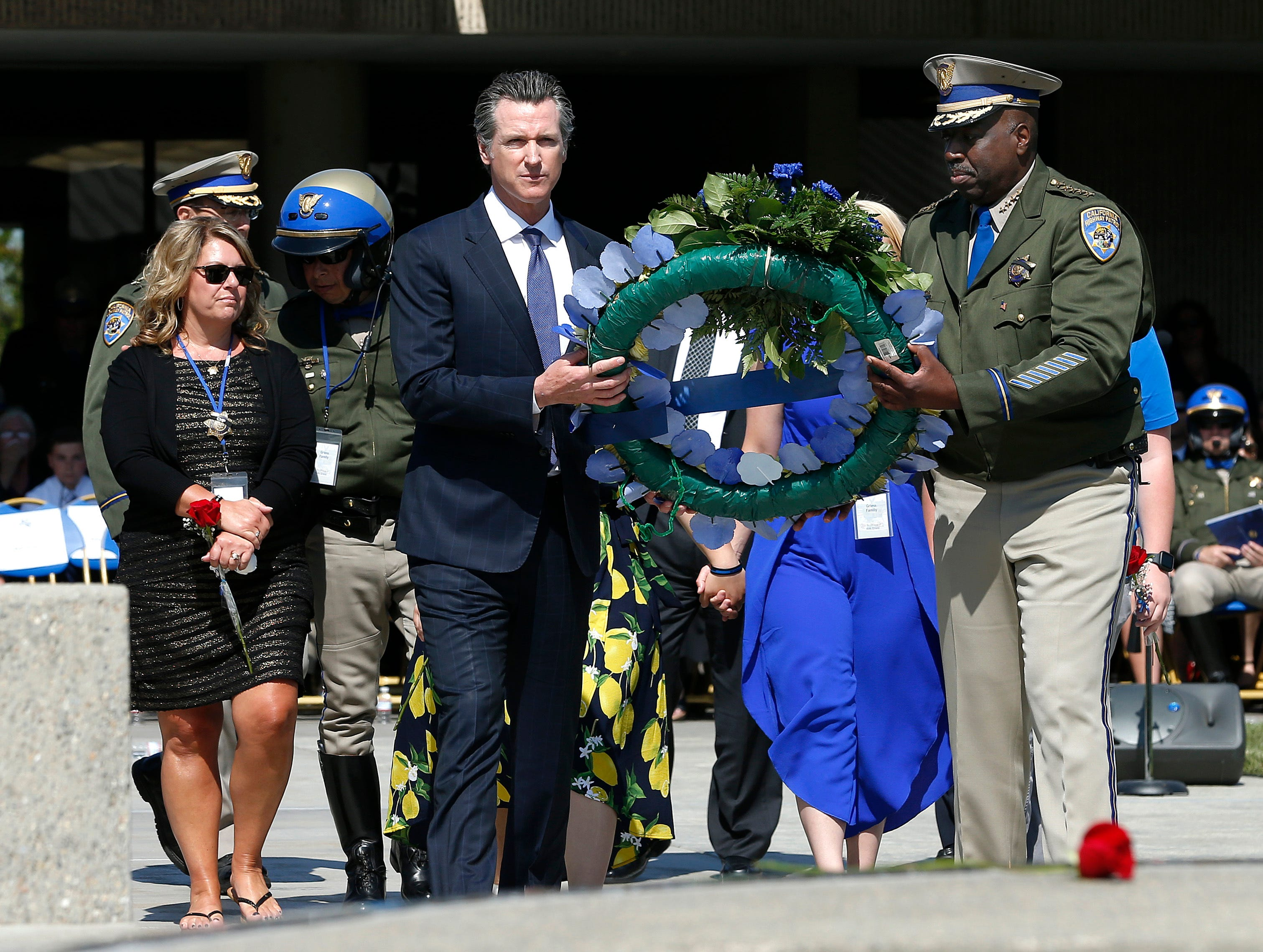Gov. Gavin Newsom, center left, and California Highway Patrol Commissioner Warren Stanley, right, carry a wreath to the California Highway Patrol Memorial where the name of CHP Officer Kirk Griess was added during a ceremony at the California Highway Patrol Academy, Tuesday, May 7, 2019, in West Sacramento. Kirk Griess was struck and killed by a vehicle while conducting a traffic stop on Aug. 10, 2018. Keri Griess, the wife of Officer Griess follows behind at left.