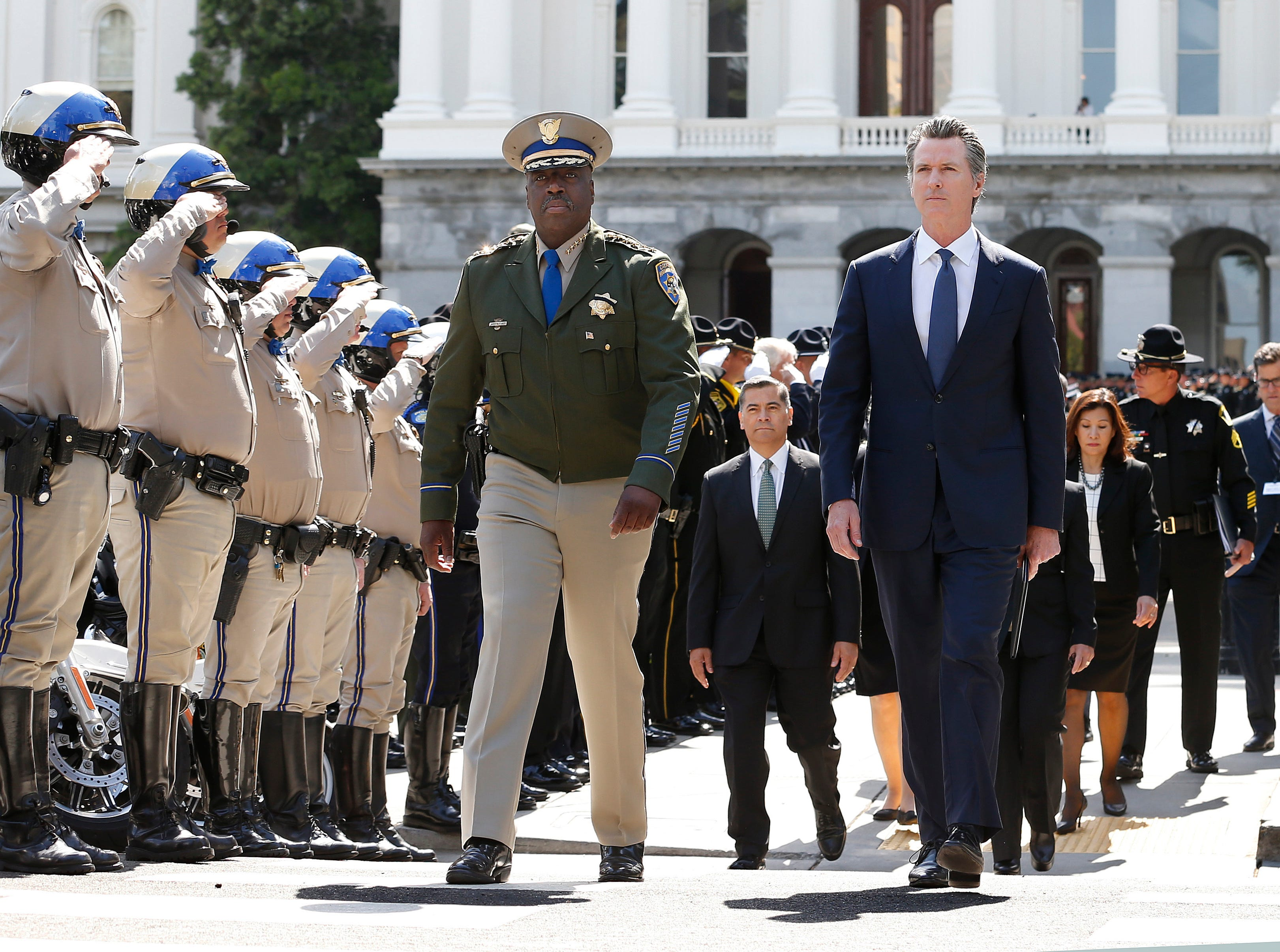 Gov. Gavin Newsom, right, and California Highway Patrol Commissioner Warren Stanley, left, pass a line of law enforcement officers as they walk to the California Peace Officers Memorial, Monday, May 6, 2019, in Sacramento. The names of eight law enforcement officers who were killed in the line of duty in 2018 have been added to the memorial.