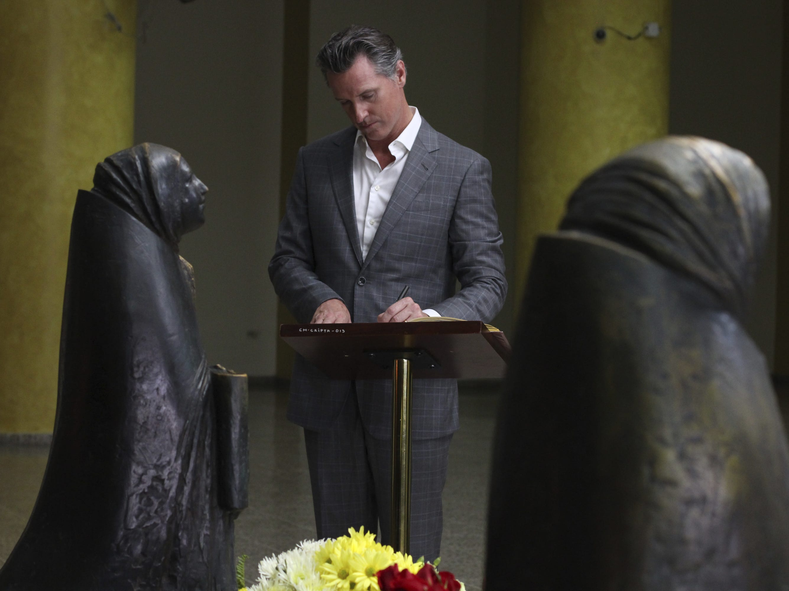 California Gov. Gavin Newsom writes a note on a book at the the tomb of Archbishop Oscar Romero at Metropolitan Cathedral in San Salvador, El Salvador, on Sunday, April 7, 2019. Romero was a Salvadoran priest assassinated in 1980 due to his advocacy for human rights and the poor.
