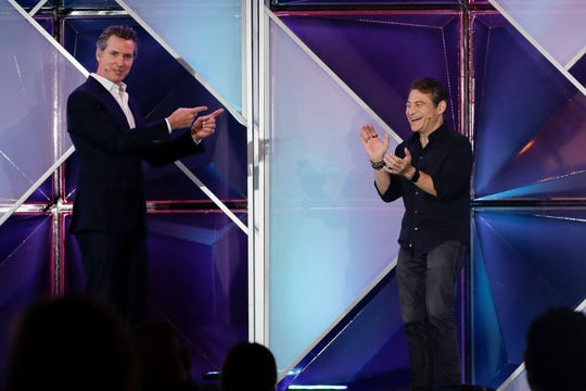 California Gov. Gavin Newsom, left, jokes with X Prize founder and chairman Peter Diamandis, right, during an announcement of a new X Prize aimed at helping combat wildfires, during the Near Future conference, Friday, May 10, 2019, in San Diego. Newsom and Diamandis announced the prize Friday, saying the prize will focus on new ways to detect wildfires before they happen and reduce their spread if they occur.