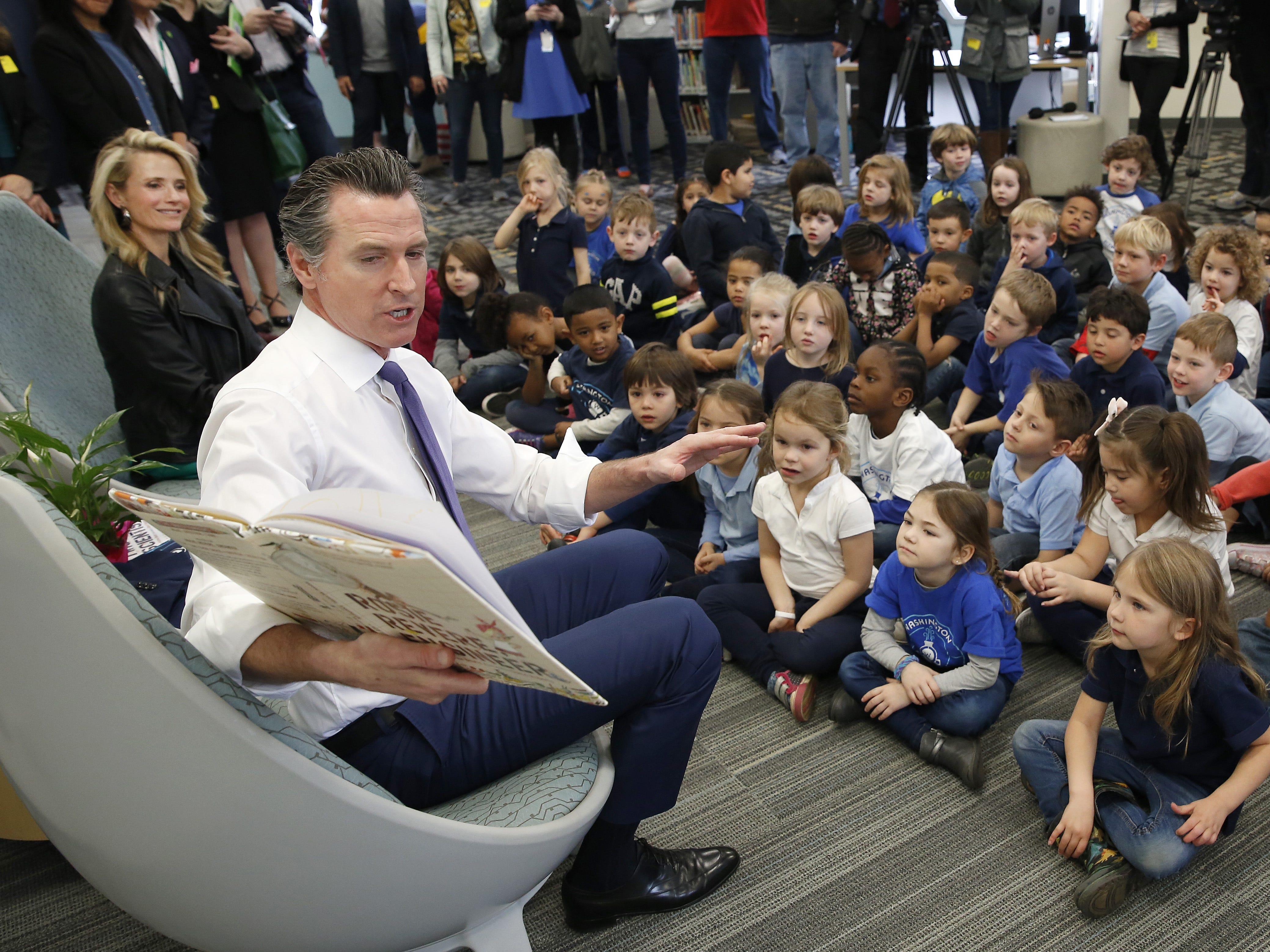 Gov. Gavin Newsom reads to kindergarteners at the Washington Elementary School in Sacramento on Friday, March 1, 2019. Newsom, accompanied by his wife, Jennifer Siebel Newsom, left, visited the school to celebrate Read Across America Day.