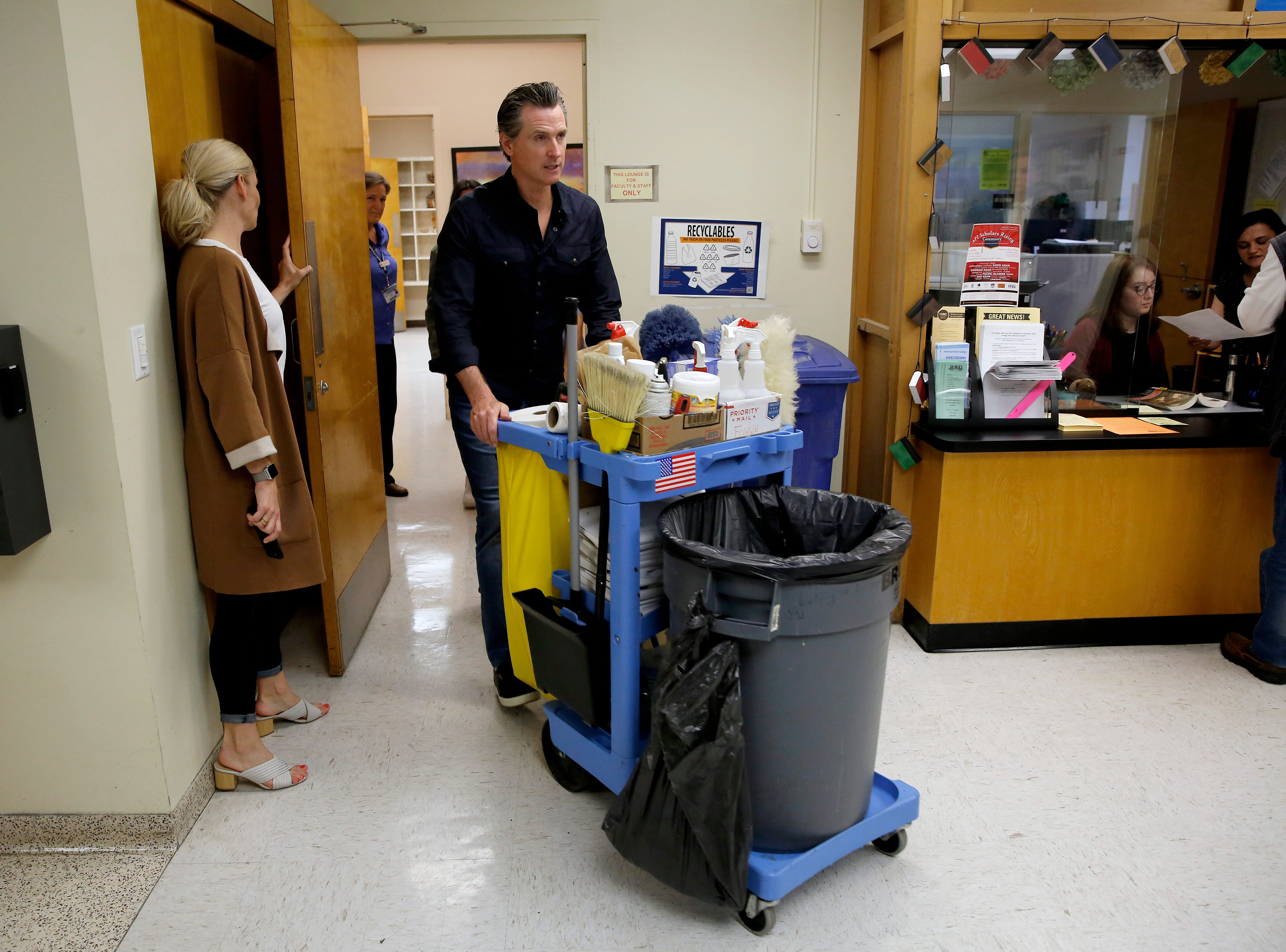 Gov. Gavin Newsom pushes a utility cart while helping the maintenance staff at American River College on Wednesday, May 1, 2019, in Sacramento.