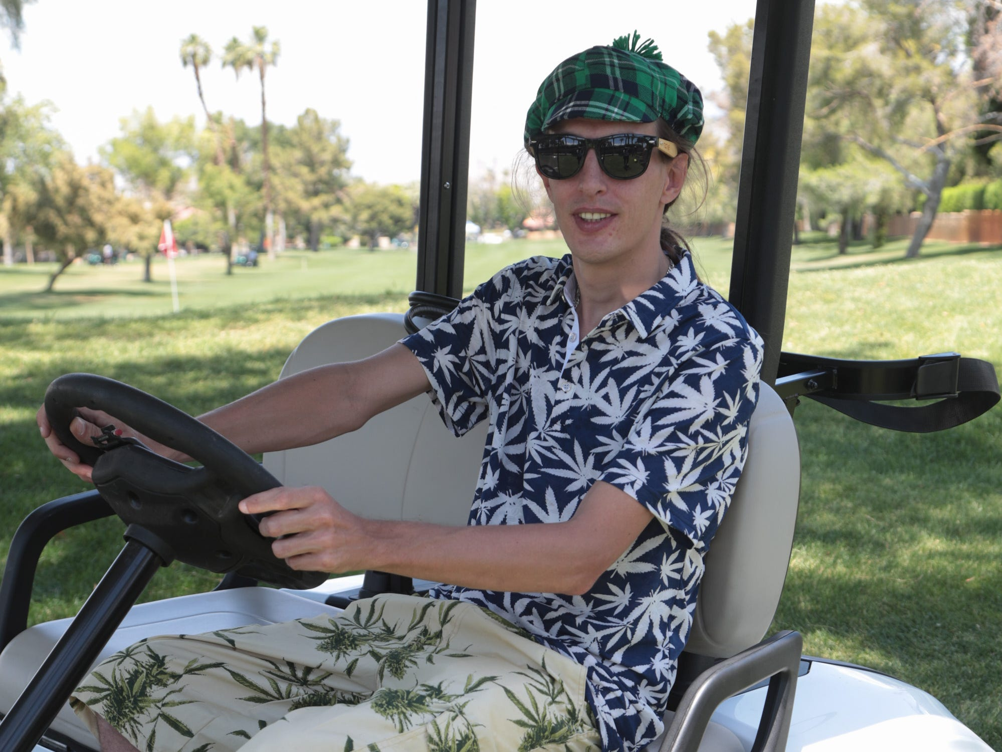 Quentin Dusastre, Director of Operations at the Coachella Valley Cannabis Alliance Network, checks in with groups of golfers at the organization's first charity golf tournament, Palm Desert, Calif., May 11, 2019.