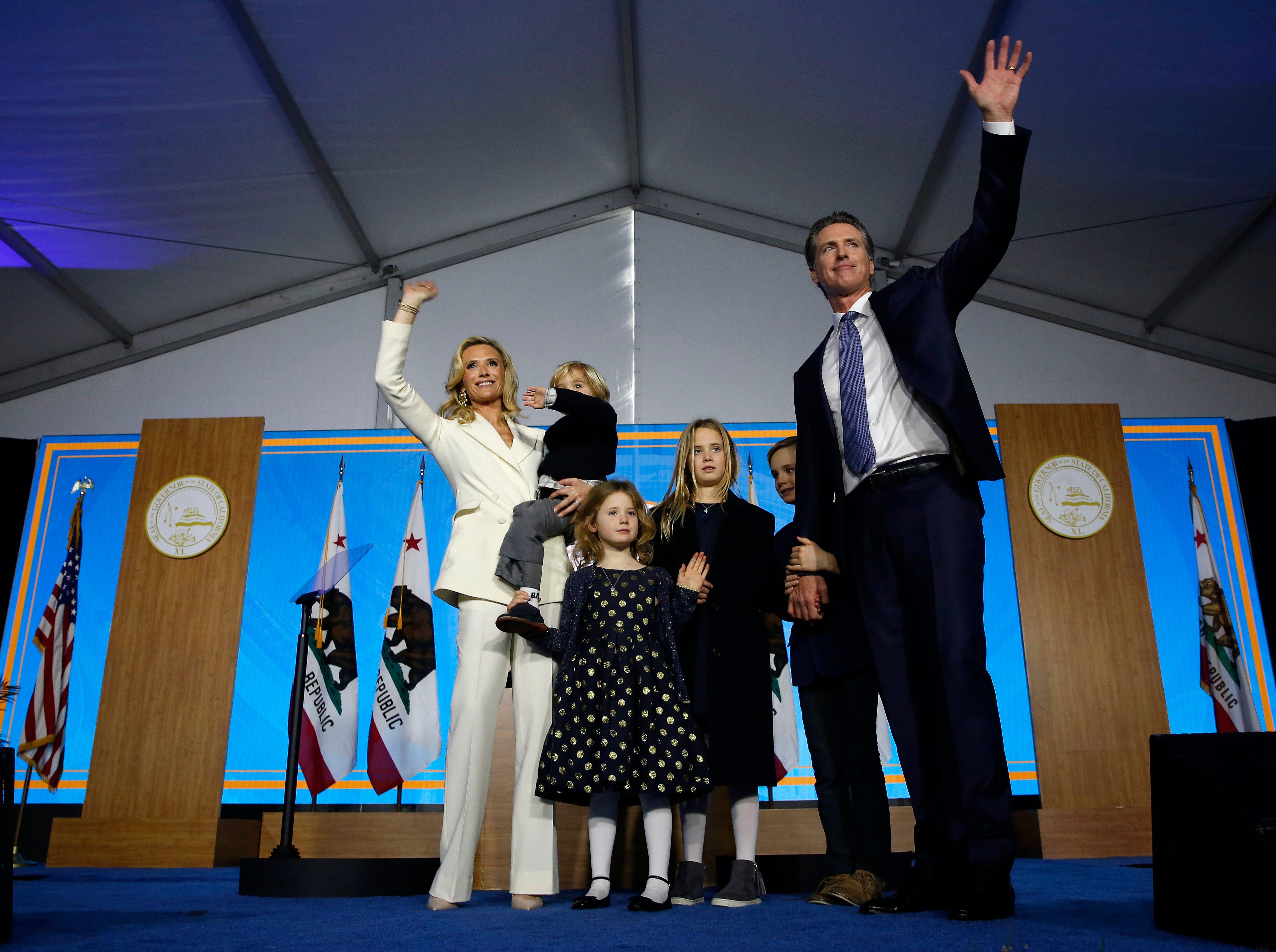 Gov. Gavin Newsom and his wife, Jennifer Siebel Newsom, wave with their children after Gavin took the oath office on  Jan. 7, 2019, in Sacramento.