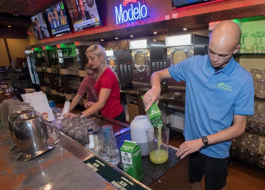 Jay Putnam, the assistant general manager of the new Cactus Cantina in downtown Pensacola, prepares the restaurant's signature margarita mix for a private party on Monday.