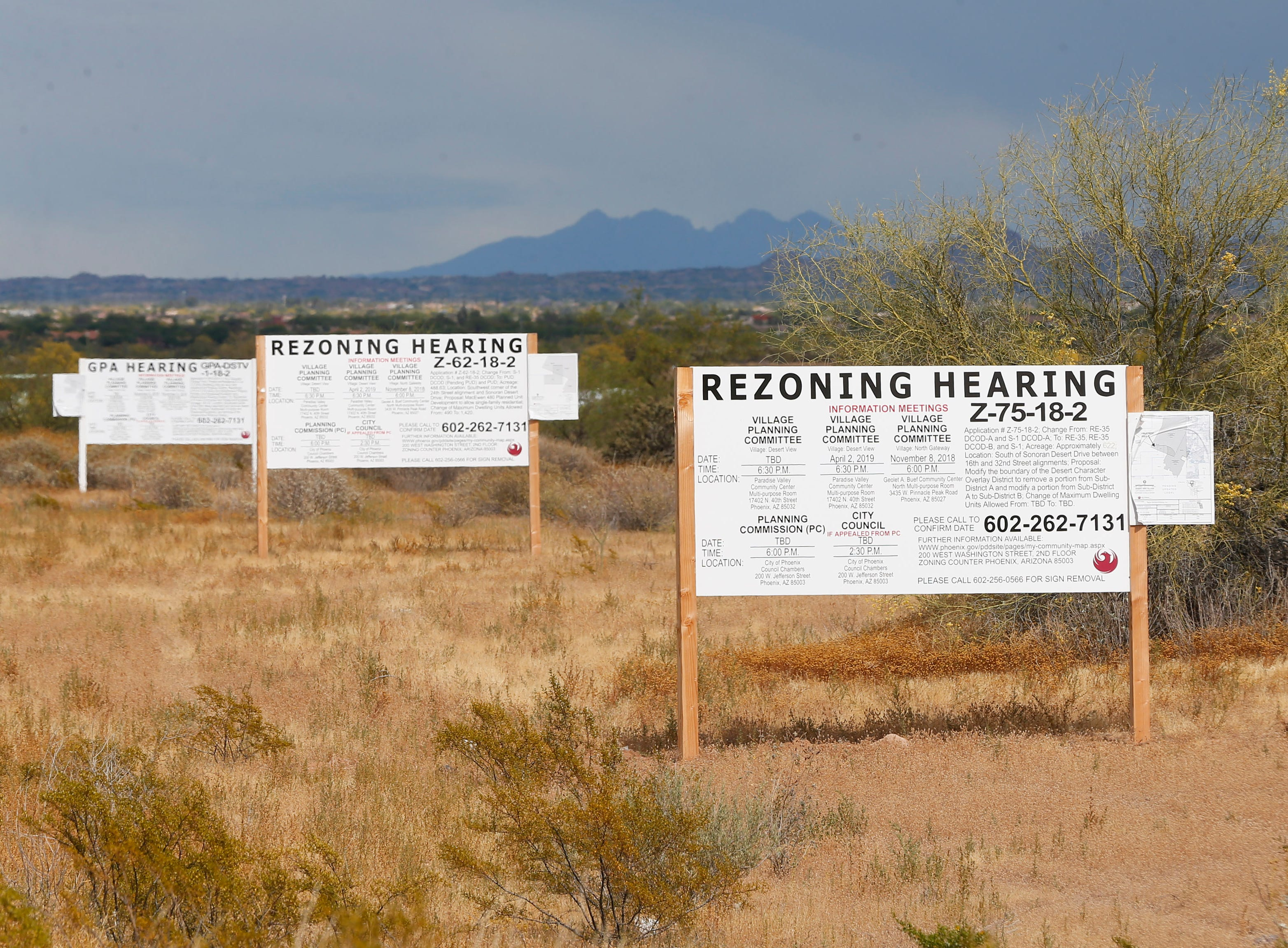 Signs for zoning change are posted on the south side of East Sonoran Desert Drive across from the Sonoran Preserve in north Phoenix May 12, 2019. Save Our Sonoran Preserve is opposed to the proposed high-density housing next to the preserve.