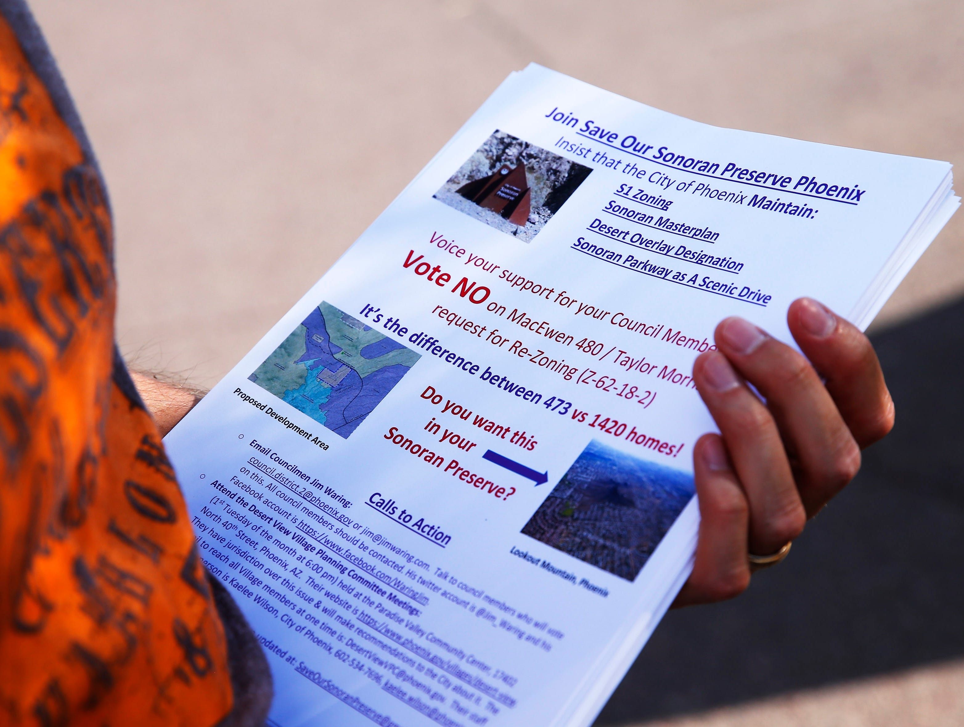 Gary Kirkilas holds flyers at the Apache Wash Trailhead in the Sonoran Preserve in north Phoenix May 12, 2019. His group, Save Our Sonoran Preserve, is opposing proposed high-density housing next to the preserve.