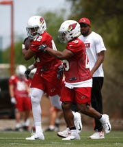 Cardinals rookie Wes Hills (42) runs a drill with teammate Steven Peoples (25) on May 10 during the first day of rookie minicamp at the Cardinals Training Facility in Tempe.