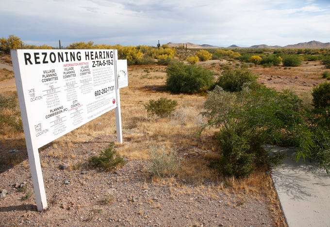 Signs for zoning change are posted on the south side of E Sonoran Desert Dr across from the Sonoran Preserve in north Phoenix May 12, 2019. Save Our Sonoran Preserve is opposed to the proposed high-density housing next to the preserve.