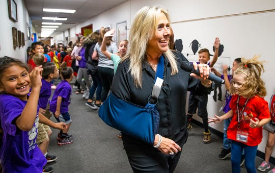 Acacia Elementary School principal Christine Hollingsworth dances in the hallway to celebrate students' reading achievements on Thursday, May 9, 2019.