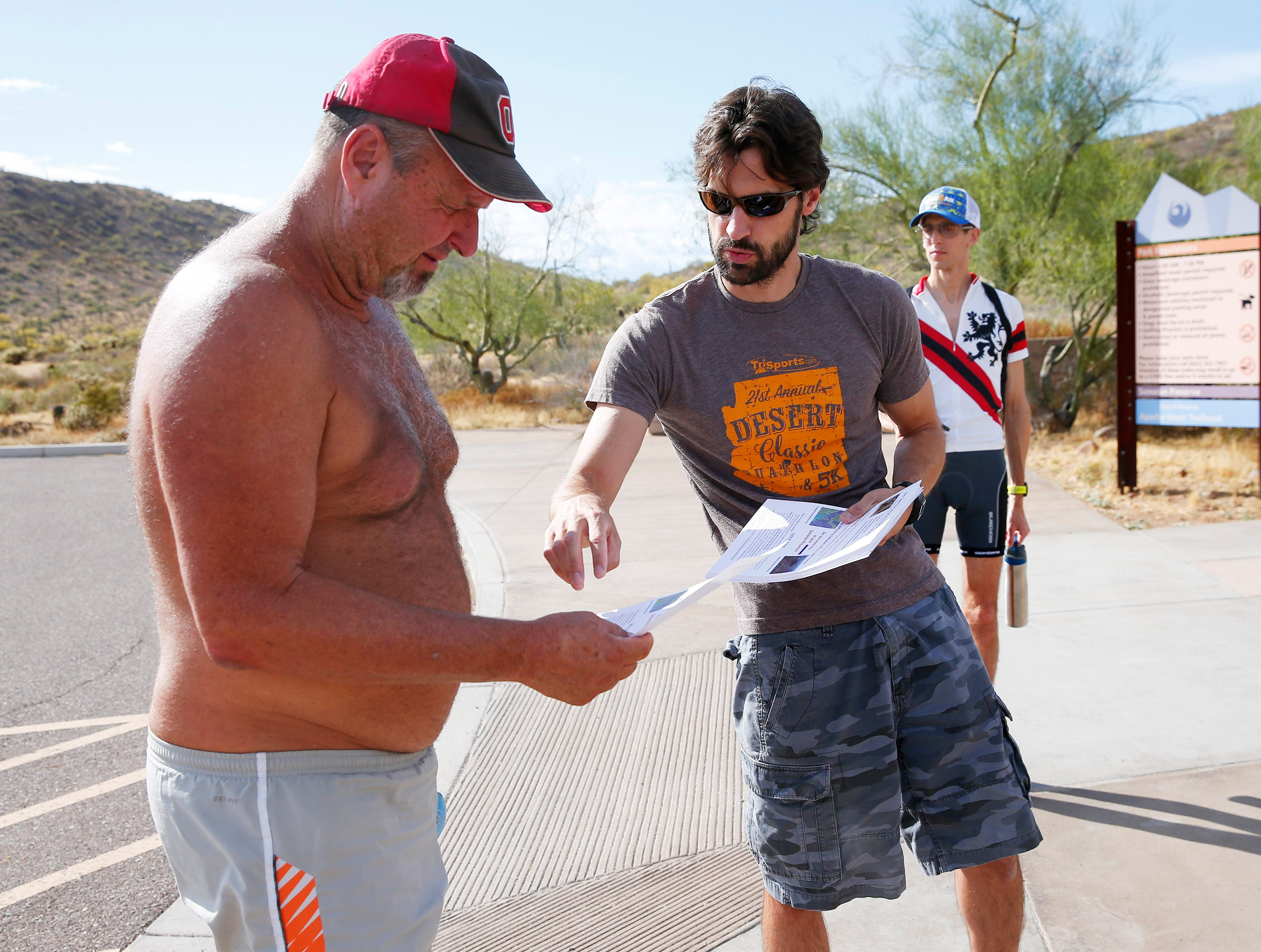 Gary Kirkilas (center) hands out a flyer to Bobby McGhee at the Apache Wash Trailhead in the Sonoran Preserve in north Phoenix May 12, 2019. His group, Save Our Sonoran Preserve, is opposing proposed high-density housing next to the preserve. Behind him is Daniel Centilli, also with the opposition group.
