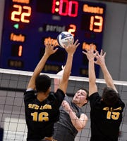 Northeastern's Kyle Williams hits the ball past Red Lion blockers Logan Axe, left, and Morgan Townsend during the York-Adams League boys' volleyball semifinal game, Monday, May 13, 2019.