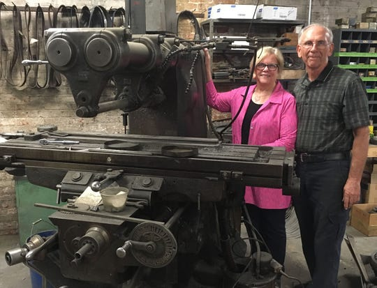 Ellen and Bob Ehlenbeck stand next to a horizontal milling machine that is at least 100 years old. Ellen recalls, as a child, she thought the top of the machine looked like a metal praying mantis.