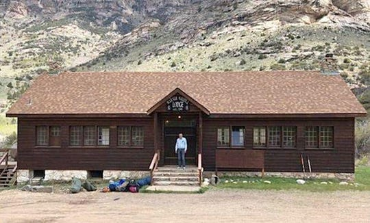 In this May 2018 photo provided by the Elko Lion's Club, Warner Whipple poses in front of the historic lodge baring his name in Lamoille Canyon, Nev., before it was destroyed on Sept. 30, 2018, in an explosive wildfire that leveled most of an 80-year-old youth camp in the Ruby Mountains southeast of Elko. Volunteers plan to return to the Lion's Club's Camp Lamoille in June to begin a $1 million rebuilding effort. (Chuck Stout/Elko Lion's Club via AP)