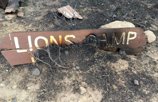 This October 2018 photo provided by the Elko Lion's Club, shows a charred sign at the Lion's Club Camp in Lamoille Canyon, Nev., that was destroyed on Sept. 30, 2018, in an explosive wildfire that leveled most of an 80-year-old youth camp in the Ruby Mountains southeast of Elko. Volunteers plan to return to the Lion's Club's Camp Lamoille in June to begin a $1 million rebuilding effort. (Delmo Andreozzi/Elko Lion's Club via AP)