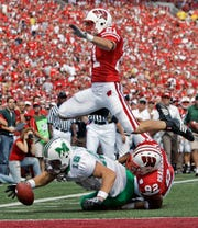 Marshall tight end Lee Smith (16) drops the ball after a 25-yard reception as he reaches for the end zone with Wisconsin's Matt Shaughnessy (92) and Chris Maragos (21) defending during the first half of a NCAA college football game Saturday, Sept. 6, 2008, in Madison, Wis. Smith recovered the ball short of the end zone. (AP Photo/Morry Gash)