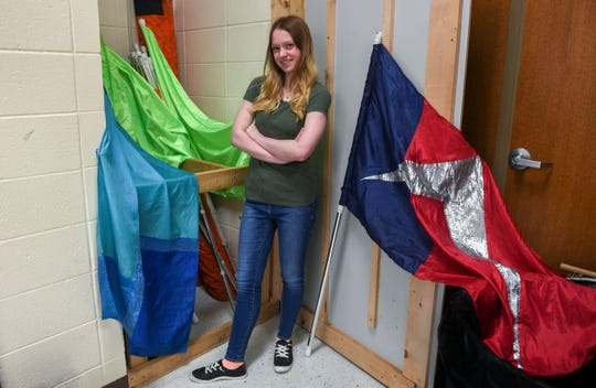 Alexis Kulm stands beside flags and banners she uses as a member of the color guard Monday, May 13, 2019 at Washington High School in Sioux Falls. She plans to attend Dakota State University to major in cyber operations. She's one in the first set of quadruplets to graduate from the Sioux Falls School District in recent history.