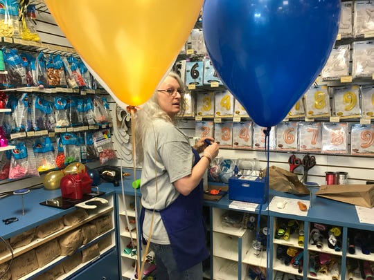 Party Land Assistant Manager Sandra Glodrey fills a balloon order for a graduation party. Party suppliers in Sioux Falls are feeling the effects of a global helium shortage.