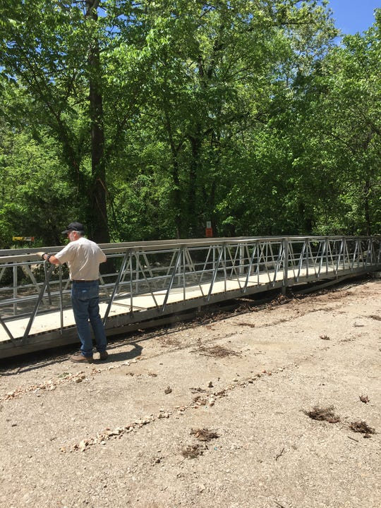Heavy equipment operator  Bob Holt surveys the shooting range bridge after it was dragged out of Camp Creek.
