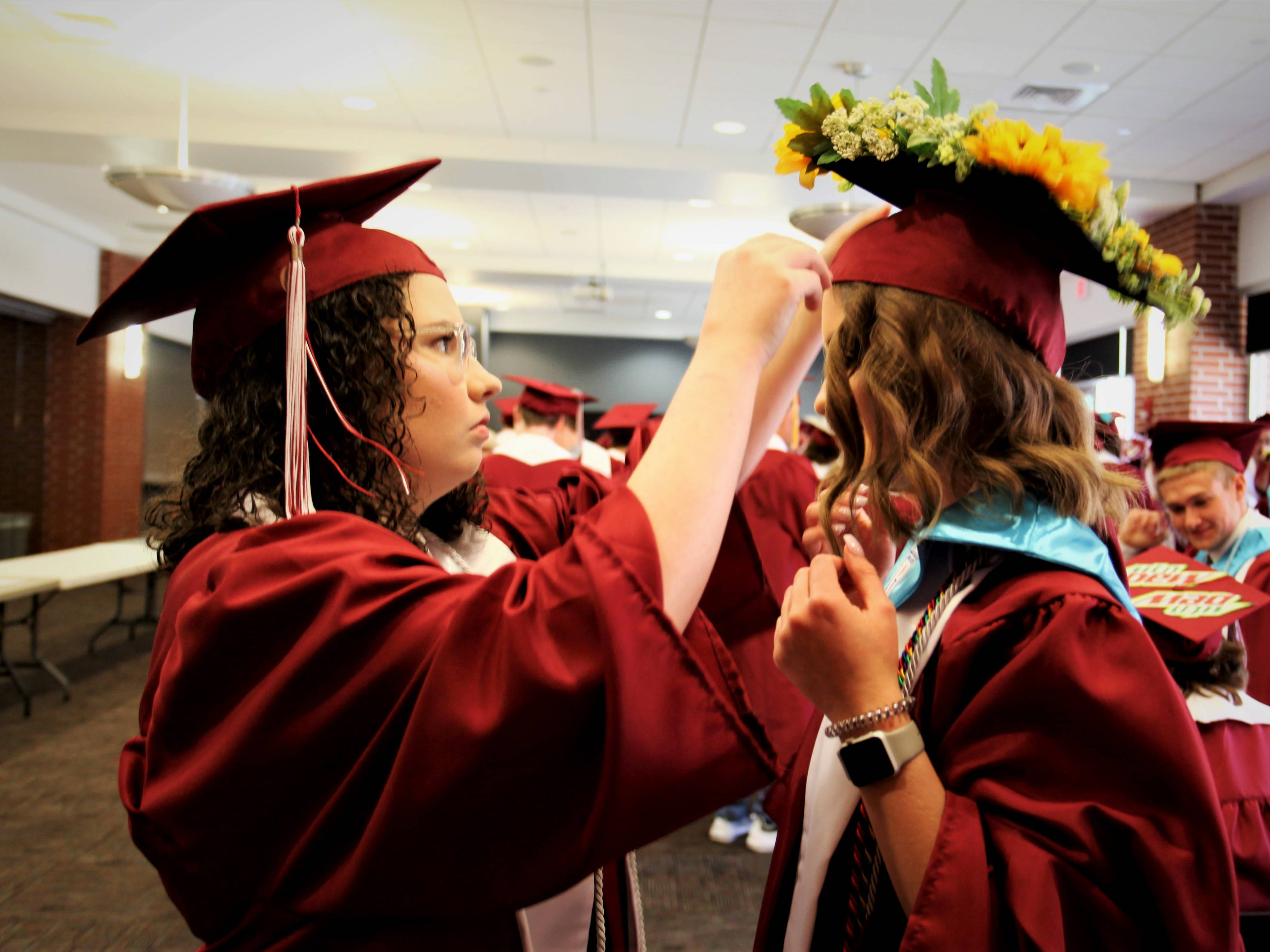 Mckenzie Morgan-Irish, left, adjusts Lily Gardner's cap before Logan-Rogersville High School's graduation Sunday, May 12, 2019, at O'Reilly Family Event Center.
