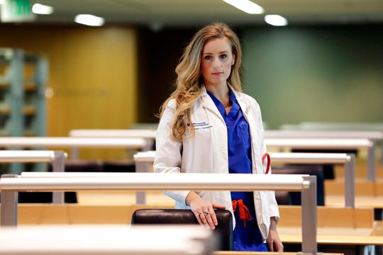 In this May 2, 2019, photo, Savanah Harshbarger, a medical student at Duke University, poses for a photo on campus in Durham, N.C. Harshbarger estimates she did as many as 10 pelvic exams last year on patients who were under anesthesia for gynecologic surgeries. Bills introduced in roughly a dozen states this year would require that women undergoing gynecological surgeries give explicit approval to a pelvic exam beforehand. It's a step that some medical experts say is an unnecessary intrusion into care. (AP Photo/Gerry Broome)